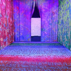 An immersive room with hand cut paintings on the walls and floor